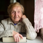 An elderly woman sitting with a book near the window.